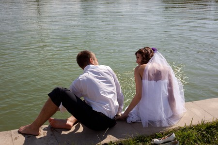 Bride and groom posing with back near water