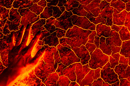 Global warming, ground volcanic eruption, Hand standing on the ground lava.