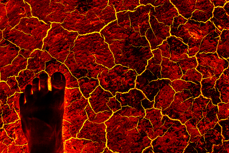 volcanic eruption: Global warming, ground volcanic eruption. Foot standing on the ground lava. Stock Photo
