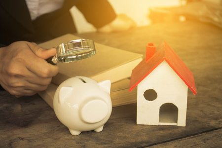 single word: Real estate investment. House and coins on table. Stock Photo