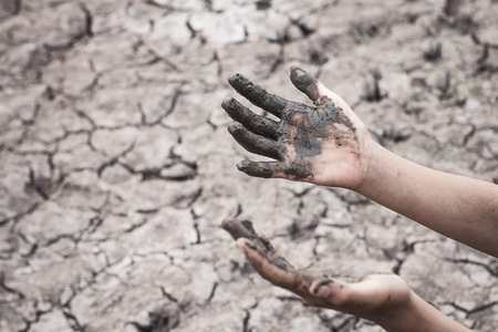 The women hand on the arid soil in hot weather lacked drinking water. Stock Photo