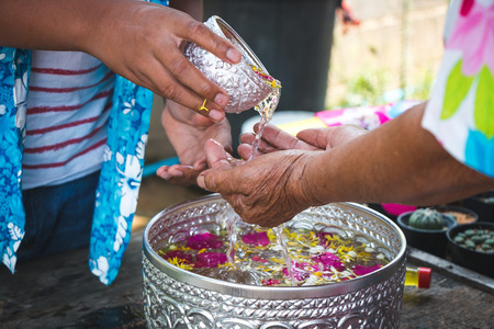 Grandchildren pour water on the hands of revered elders and ask for blessing in the Songkran festival.