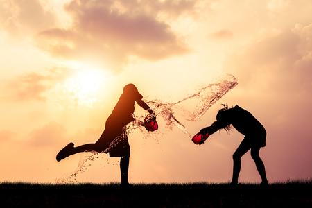 Children playing splash water on Songkran silhouette.