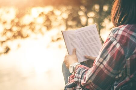Women tourists read book in quiet nature.