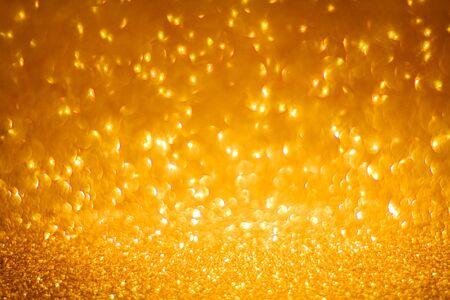 Gold shining lights sparkling glittering blurred background.