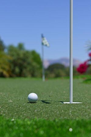 퍼 팅 녹색 구멍 옆에 골프 공. 다음 구멍이 거리에서 보입니다.