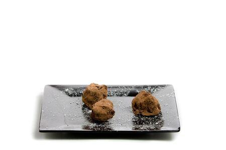 trufas de chocolate: Tres trufas de Chocolate en un plato negro con un fondo blanco Foto de archivo