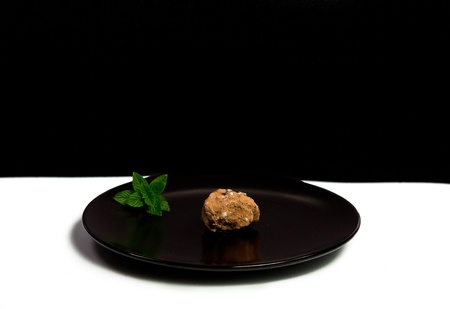 chocolate truffle: A Chocolate Truffle on a Black Plate with a mint sprig