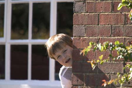 A young boy peeking around a brick wall on a sunny day Stock Photo - 799325