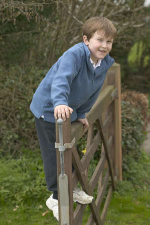 A happy young boy standing on a five bar gate Stock Photo - 799334