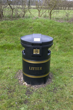 Black litter bin with gold detail in a rural setting photo