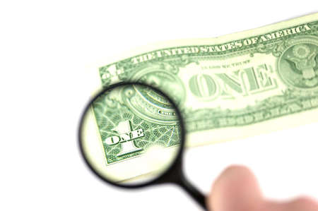 Magnifying glass looking at the one on a dollar bill photo