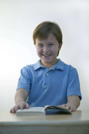 A young schoolboy sitting at a desk laughing photo