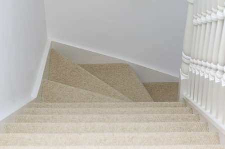 An interior shot of a view down some carpeted stairs photo