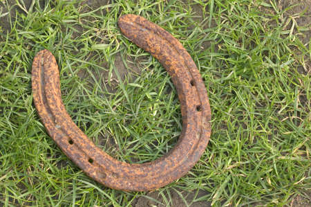 Old rusted horseshoe lying on a grass and mud background. photo