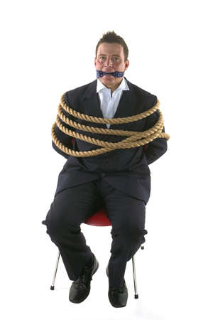 Businessman tied up with rope and gagged with his own tie. photo