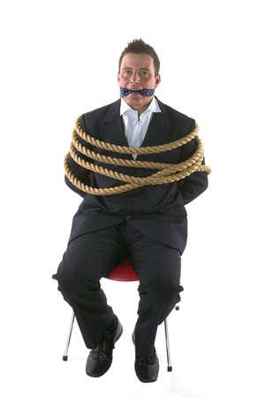 gefesselt: Unternehmer mit Seilen gefesselt und geknebelt, mit seiner eigenen Krawatte.