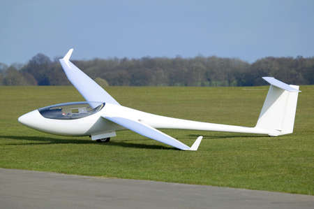 airfield: White Plane or Glider at rest on an airfield