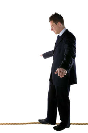 Businessman walking a tightrope, isolated on white. photo
