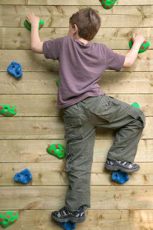 climbing  wall: Young boy climbing a garden rock wall.