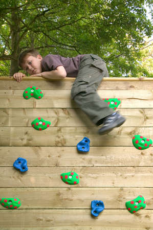 ascend: Young boy going over the top of a garden rock climbing wall. Motion blur on his leg. Stock Photo