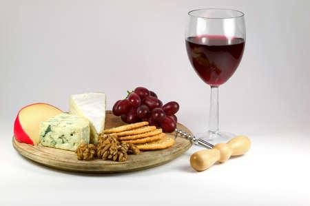 tabla de queso: Tabla para el queso y un vaso de vino tinto. Foto de archivo