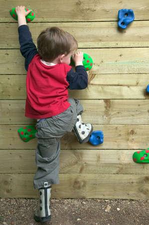 ni�o escalando: Ni�o que procura subir una pared de la roca del jard�n