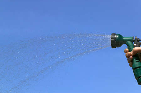 hosepipe: Water spraying from a hosepipe sprinkler, against a bright blue sky. Stock Photo