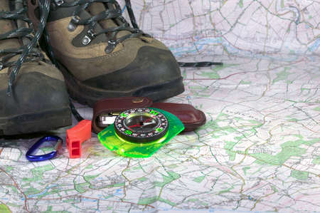 rambling: Hiking boots,compass and accessories on a map background Stock Photo