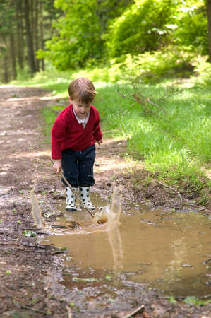 muddy: Toddler splashing in a muddy puddle with his stick.