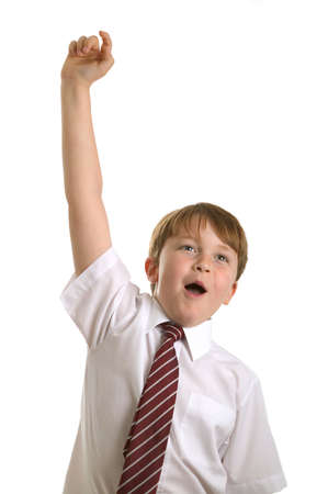 Schoolboy with his hand raised ready to answer a question. Isolated on white.