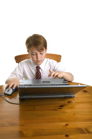 Young schoolboy using a laptop sat at a desk, isolated on white.