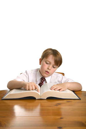 scholastic: Schoolboy reading from an encyclopedia whilst sat at a desk, isolated on white.