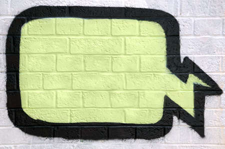Graffiti thought bubble sprayed on a brick wall, enter your own text. Editorial