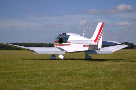 seater: White light aircraft on a grass runway.