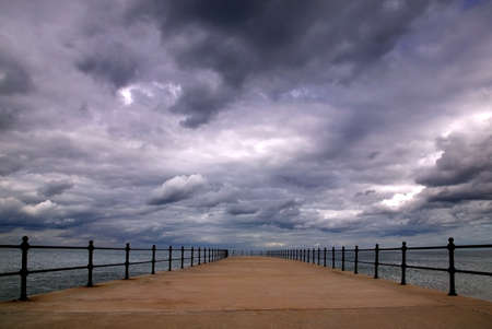 diminishing: Storm clouds forming over an empty pier.