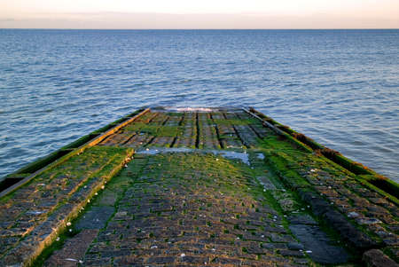slipway: Cobbled boat slipway leading into the sea, lit by the morning sun.