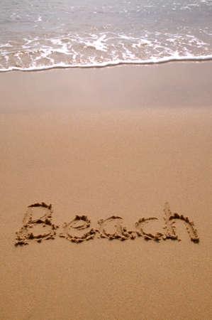 Beach written in sand at the beach. photo