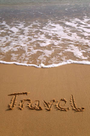 Travel written in the sand on a beach. photo