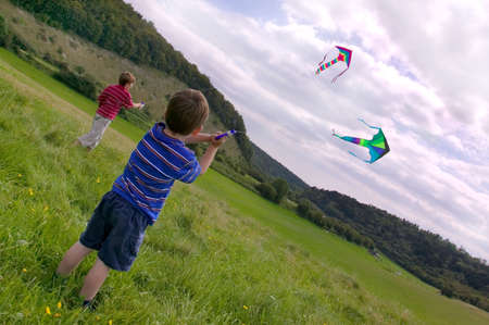 Two young boys flying their kites in a meadow. photo