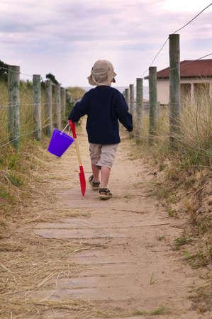 despite: Toddler off to the beach, despite the gloomy weather! Stock Photo