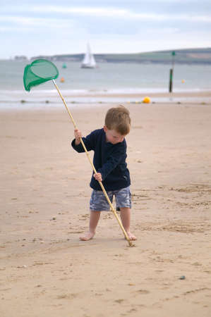 Toddler using his net to do a sand drawing on the beach. photo