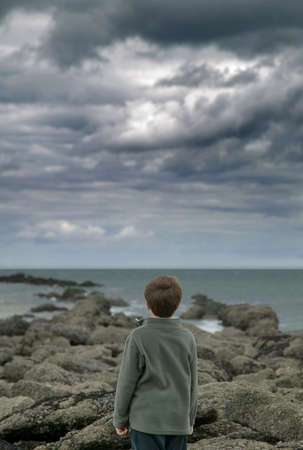 Young boy looking out to sea as storm clouds approach. Stock Photo - 1577337