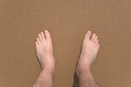 viewpoint: Downward view of a mans legs and feet at the beach.