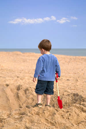 Toddler on the beach admiring a huge hole he has just dug in the sand. photo