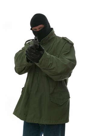 kidnapper: Armed man in a balaclava aiming a handgun at his target. Stock Photo