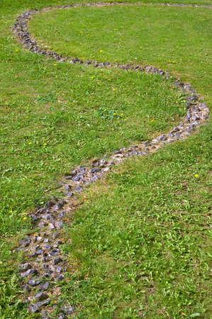 Winding flint path through green grass.