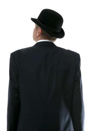 Homme d'affaires dans un chapeau de chapeau melon regardant jusqu'au futur. Vue arrière.