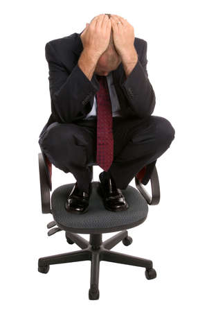 mistake: Businessman crouched on an office chair with his head in his hands. Stock Photo