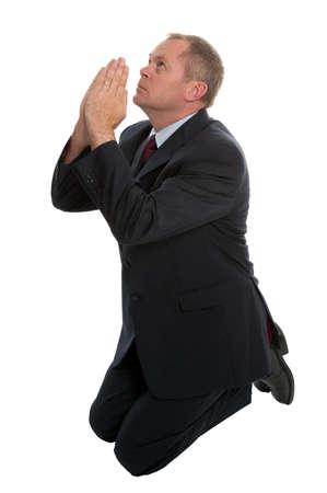 Businessman on his knees praying.